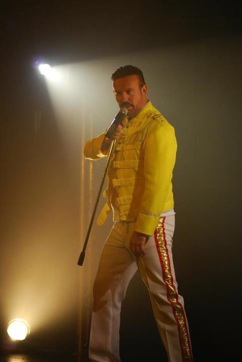 A freddie mercury tribute act singing on stage
