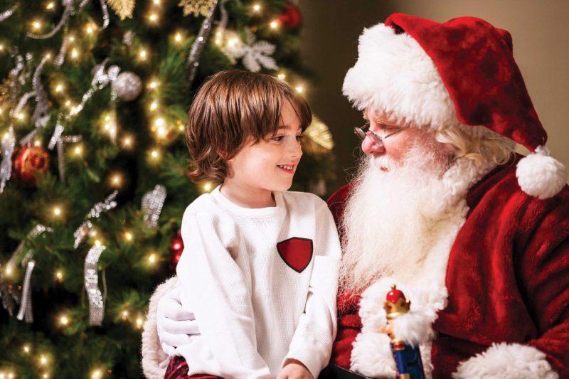A child sits on Santa's lap in front of a Christmas tree