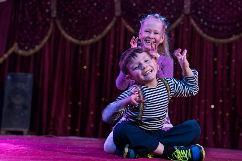 Two children sit on stage making signs with their hands at a theatre