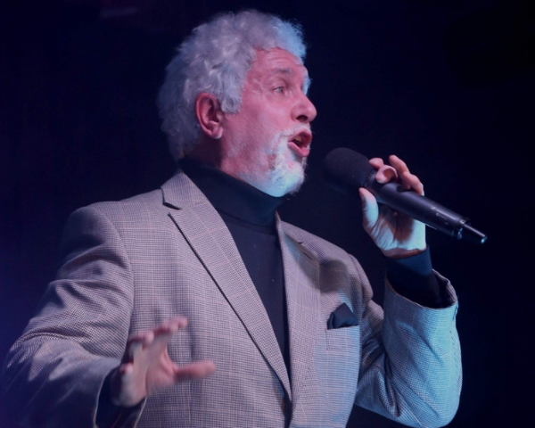 The tibute act of Tom Jones singing into a microphone