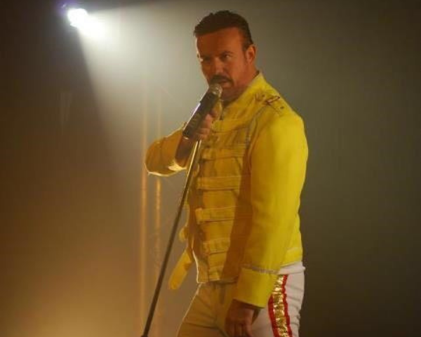 The tribute act of Freddie Mercury singing into a microphone