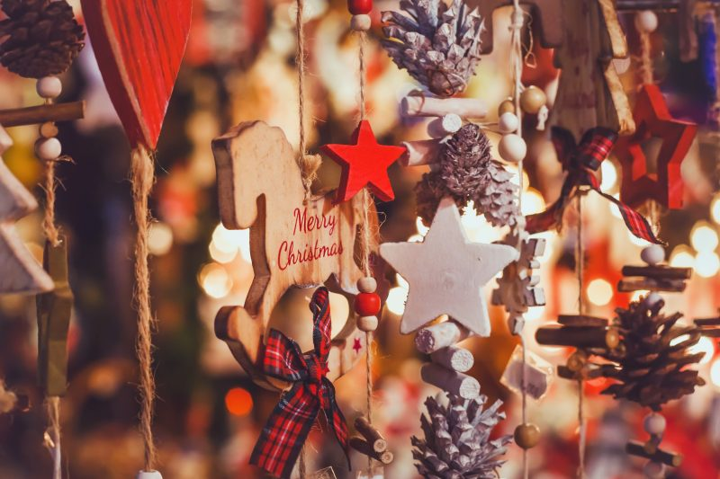 wooden decorations hang from a stall at a christmas market