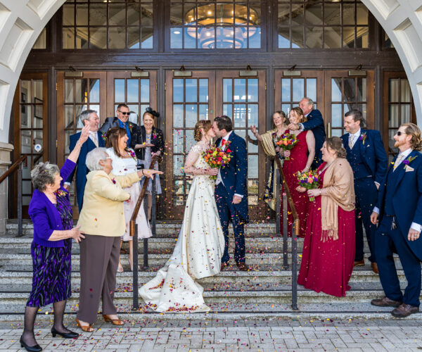 A married couple kiss on the steps of Spanish City as guests clap